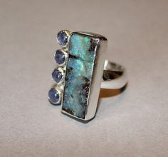 Tantalizing #tanzanites complements a big Aussie #boulder #opal ..  handmade rings by MyFascinationStreet