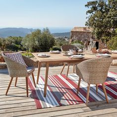 Une salle à manger de jardin en osier tressé avec coussins colorés et tapis rayé, sur une terrasse surplombant le paysage.