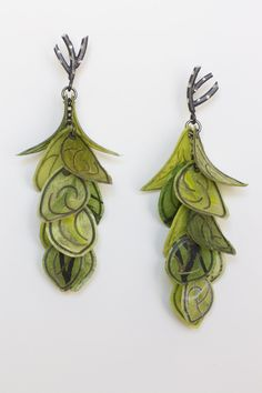 Green Flip Earrings by Carol Windsor. A flurry of vibrant green petals cascades from twig-shaped sterling silver posts. Each petal is meticulously created by the artist by laminating sterling silver wire between sheets of paper. Sealed with acrylic for a long-lasting, water-resistant finish. Limited edition of 10.