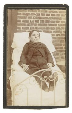Young boy posed outside on a bed. Victorian post mortem photography may seem strange, but for some families it was their only opportunity to have a memento of their loved one as photography was expensive at the time. Sometimes the dead were posed as if alive and sometimes are of children and babies due to the high death rate among this group at the time.