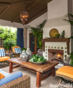 In the covered outdoor living room of a 1920s Santa Monica, California, home, designer David Dalton created a relaxing year-round space with insulated Sunbrella curtains and a fireplace decorated with custom Talavera tiles by Mission Tile West. Wicker chairs by Palecek. Indonesian coffee table, Moroccan urns, and lantern from Berbere World Imports.