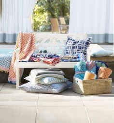 Decorative throws, like these by @johnrobshaw,  create an inviting poolside atmosphere.
