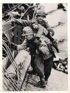 1945 - Captain J. McMahon, of the U.S. 9th Army, carrying a child over a bombed bridge at the River Elbe, Tangemunde. The bridge was blown up by retreating German troops.