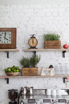 Estanterías con cajas de madera recicladas, plantas aromáticas, relojes y balanzas vintage #DecorarLaCocina