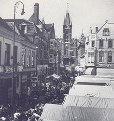 Stoombootdiensten van Eindhoven naar: Deze foto van Martien Coppens geeft de sfeer weer van een gezellige markt met op de achtergrond het voormalige stadhuis foto uit: Het lonkende licht : herinneringen aan Eindhoven tussen de jaren 1932 en 1982  van Martien Coppens en Frits van Griensven