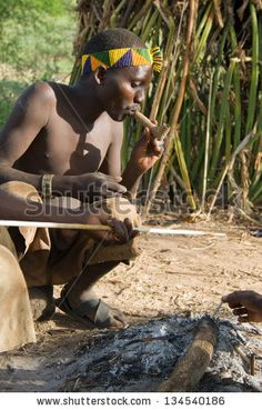 LAKE EYASI, TANZANIA - FEBRUARY 18: An unidentified man from Hadza tribe, smokes a traditional pipe, on February 18, 2013 in Tanzania. Hadzabe tribe threatened by extinction. Stock Photos, Royalty-Free Images and Vectors - Shutterstock
