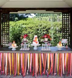 Love the streamer look.  Another pinner said: this inspired me to layer different colored plastic table skirts and cut the top one into strips so the bottom color can peek through in the background!    At this wedding in Sonoma, Calif., more than 50 ribbons in shades of pink, yellow and orange were hung in a row from the cake table, making far more of an impact than a tablecloth ever would.