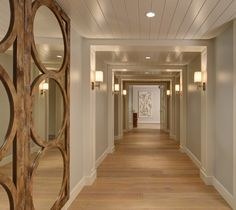 Tongue and groove ceiling, neutral paint colours and wall lighting make this an inviting hallway #hallways #lighting #ceiling