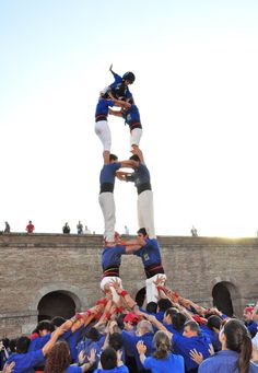 Members of the Castellers of Vila de Gràcia, a human tower-building club in Barcelona, perform in a town square, as passersby look on.