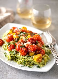 This homemade garlicky pesto spaghetti squash is topped with yellow and red roasted tomatoes, the perfect low calorie alternative to an Italian favorite.