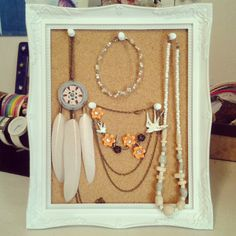Use a corkboard, a picture frame, and push pins to organize your jewelry!