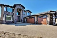 Luxury custom home with over 5700 sq ft of beautiful living space situated in the desirable community of Kinniburgh! The main level boasts 9 ft ceilings, gorgeous curved staircase & hardwood floors th