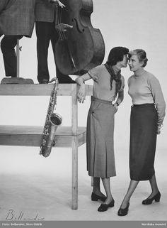 Två modeller klädda i polotröja och kjol, modellen till vänster bär scarf och lutar sig mot ett bord. På bordet står två män, en basfiol och en saxofon. Fotograf: Sten Didrik Bellander, ca 1950-1955