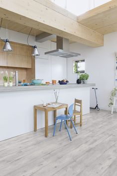 A sense of softness fills this modern kitchen, thanks to the light grey laminate flooring. These concrete-coloured planks look amazing. Find out more laminate flooring ideas here. Grey Laminate Flooring, Vinyl Flooring Kitchen, Kitchen Vinyl, Concrete Kitchen, Wide Plank Flooring, Best Flooring, Diy Flooring, Bedroom Flooring, Concrete Wood