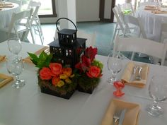 Neat Centerpiece with Orange Roses in Wooden Boxes Placed around Rustic Lantern http://busseysflorist.com/wedding-flowers/