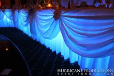 Think Spring and be bold. Blue wedding uplighting under head or sweetheart table
