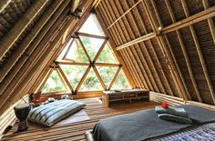 Cozy bamboo living room with big triangular windows. Dream house in Bali. Off grid bamboo house nestled in Bali highlands near volcano. Sustainable house made entirely from bamboo using water wheel to generate electricity.