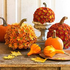 Update a classic display of pumpkins with a flowery makeover of blooms in seasonal shades. Begin carving as you would with a jack-o'-lantern, removing the seeds and pulp. Using a drill or nail, make holes just wide enough for flower stems to fit through. Cut the flower stems about a half inch from the flower head, and poke the stems into the holes. Keep the inside of the pumpkin moist; flowers will last two or three days.