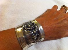 Sterling silver wide rose cuff bracelet with detail leaves and buds from an old brush back. $675.00, via Etsy.