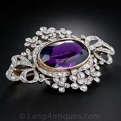 Large French Antique Amethyst and Diamond Brooch and Pendant, This Victorian brooch and pendant combo radiates with a luscious deep purple Siberian amethyst, weighing 17.75 carats. The majestic gemstone is set in a yellow gold bezel and is fancifully framed in sparkling flowers and flowing ribbons of old mine-cut diamonds. This magnificent jewel is finely handcrafted in platinum over 18 karat yellow gold and is fitted with its original removable pin mechanism.