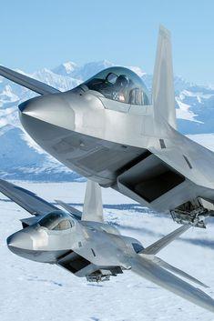 Dos F-22 del 90th FS de la USAF volando sobre Alaska con las bodegas de armas abiertas, mostrando misiles Sidewinder.
