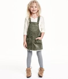 Bib overall dress in cotton corduroy with adjustable suspenders. Bib pocket, side pockets, snap fasteners at sides, and decorative lace trim at hem.