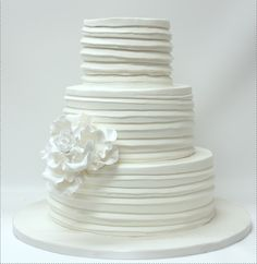 I like the cake, maybe with a orange wrap in center and stacked pearls at the bottom of  the layers