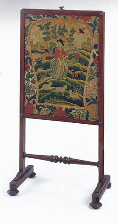 A Classical Mahogany Needlework Fire Screen, 19th century. With an eighteenth-century needlework panel for a chair back, sewn into a later needlework border to fit retangular frame, 36 in. high, 17 3/4 in. wide, 11 1/2 in, deep