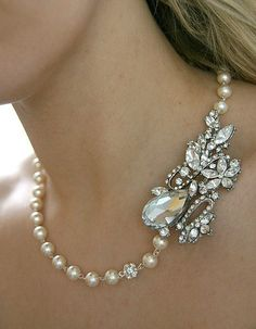 antique brooch showcased on pearl strand..pin the brooch carefully on the necklace