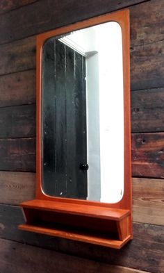 Stylish simplicity of Danish design is epitomised in this beautiful wall mirror.  Its lines and proportions give it an under-stated elegance that cannot fail to raise a smile every time you look in it, or even just look at it.  Crafted from teak, tapering slightly from top to bottom and featuring a storage cubby hole set into a handy shelf, this piece offers style, beauty and practicality in one compact package.