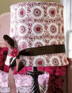 Add your own personal touch to a lampshade by wrapping fabric around a self-stick shade. Finish off with ribbon and a floral pin.