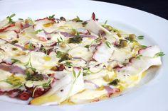 Crudini de Pulpo de Gaston Acurio. cortar pulpo en laminas y acomodarlo en plato frio. cubrir de un pesto casero y una vinagreta de parmesano y alcaparra. finalmente chorro de aceite de oliva.