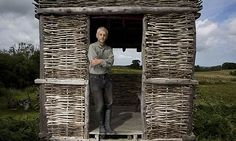 Jon Harold stands in a bird hide that was constructed on the farm using traditional carpentry methods at Moelyci Farm, Bangor, Wales