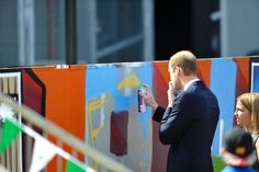 Britain's Prince William uses a spray to paint a wall, Wednesday, April 23, 2014, in Adelaide, Australia.