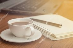 A coffee cup and blank notebook, A coffee cup on the office desk background in the the soft light with sunrise simulation. #coffee #cup #office #notebook #business #light #warm #happy