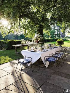 At the Bedford, New York, home of fashion designer Ralph Lauren, a terrace is shaded by a linden tree and vintage wrought-iron chairs encircle a table set for an alfresco dinner.
