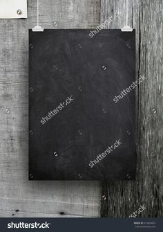 Close-up of one blank blackboard frame hanged by clips against grey weathered wooden background