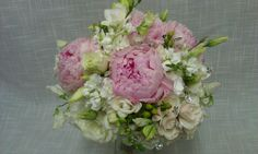 Elegant pink and cream bridal bouquet includes Sarah Bernhardt peonies, hydrangea, freesia, sweet pea, lisianthus, stock and spray roses.