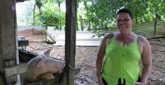 Yamileth, a microcredit client of ACRG in Costa Rica poses with pigs she was able to buy with her microloan