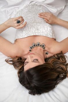 Our images are featured in this blog!! bride on hotel bed in wedding dress, blue stone wedding engagement ring and matching necklace | Flowers by Festivities | Sheraton Hotel in Bloomington, MN | Hair by Hair by Heidi | Photo by Memories in Time Photography | Planned by Sixpence Events & Planning | Makeup by KMT beauty | Garters by Three Comforts | Jewelry by Style by Cia | Dress from Bridal Aisle | Model Katie Lietz