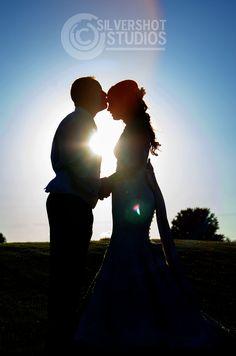 Bride groom wedding portrait silhouette sunset sun flare
