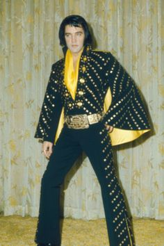 """Black Butterfly 1972 - This suit is, basically, a reversed version of the White Pyramid. The nails on the suit are tiny butterflies. One of the suits that was only worn in Vegas, and never on tour. Apparently, there were two slightly different versions of this suit. The other, which can be seen on the """"costume fitting"""" pictures, has yellow lined cape, and yellow kick pleats, and the other, which has been on display at Graceland, has gold lined cape and kick pleats."""
