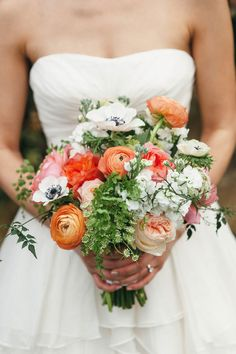 pretty bridal bouquet with ranunculus, anemones, peonies, and greenery in shades of coral and pink