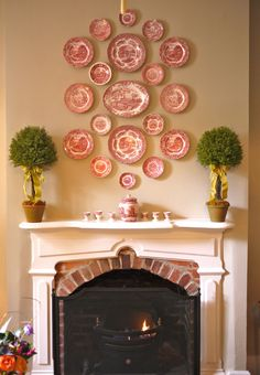 Lovely collection of red and white plates arranged above a mantel. The colors tie them all together though they vary in size and the center one is an oval platter. The topiary trees balance it out and add to the symmetry.