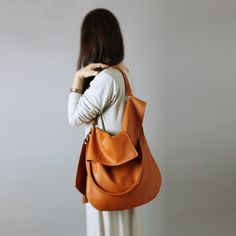 TUULI is a slouchy hobo made of soft and buttery, italian leather in orange cognac color.  It is big, simple and asymmetric.  Bag is made of 100% natural leather.  UULI is a slouchy hobo made...
