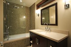 bathroom with white bathtub covered in mosaic tiles, silver round rain shower on top and moveable shower under of Shower Bathtub Combo in Your Bathroom