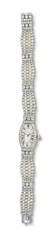 An art deco diamond and seed pearl wristwatch, by Cartier, circa 1920  The tonneau-shaped dial with Roman numerals and blued steel hands, between bezel and lugs set with brilliant and single-cut diamonds, on a graduating five-row seed pearl bracelet, spaced by brilliant and single-cut diamond bars, diamonds approximately 2.40 carats total, dial signed Cartier, numbered, French assay marks, length 17.4cm