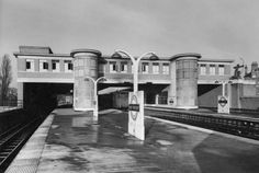 Photograph of East Finchley underground station by architect Charles Holden. Photo by S.W. Newbery. Copyright: Architectural Press Archive/RIBA Library Photos. Originally started by L. Bucknell &d R. Ellis, the design was taken over by Holden. The striking design with two semi-circular towers linked by a bridge across the platforms housing a staff canteen echoes Walter Gropius' famous model factory at the Werkbund Exhibition in Cologne from 1914. The art deco archer figure was by Eric…