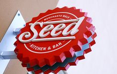 Seed Kitchen & Bar: projecting signs automatically catch the eye, why not make them compelling to look at with a sweet shape? Environmental Graphic Design, Environmental Graphics, Wayfinding Signage, Signage Design, Bar Signs, Shop Signs, Blade Sign, Restaurant Signage, Sign Board Design