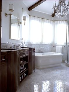 Traditional bathroom. This transitional master bathroom is designed like a luxury spa. The custom-made vanity and window treatments and specified lighting, plumbing fixtures and fittings and Carrera marble complete the look.